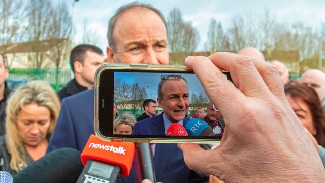 Leader of Ireland's Fianna Fail party, Micheal Martin (C) is filmed as he speaks to members of the media outside the count centre in Cork