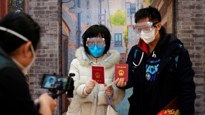 Su, 28 (L) und Jia, 29, heirateten mit Gesichtsmasken am Valentinstag in Shanghai in einem Standesamt