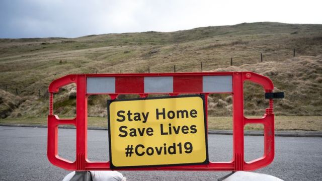 BRECON, WALES - MARCH 28: A sign on the A470 near Pen y Fan warns motorists to stay at home to save lives on March 28, 2020, in Brecon, Wales. Last weekend the area was busy with walkers. The Coronavirus (COVID-19) pandemic has spread to many countries across the world, claiming over 25,000 lives and infecting hundreds of thousands more. (Photo by Matthew Horwood/Getty Images)