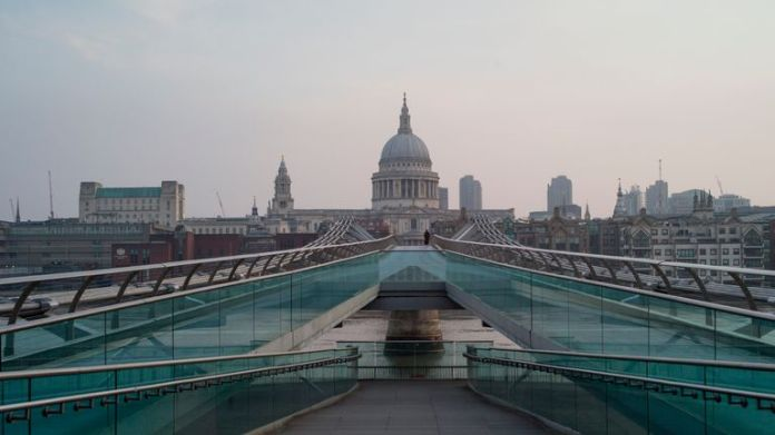 London, ENGLAND - April 10: A lone woman walks over Millennium Bridge on April 10, 2020 in London, England. There have been over 60,000 cases of COVID-19 coronavirus in the UK and 7,000 deaths. The country is in its third week of locking measures to slow the spread of the virus. (Photo by Dan Kitwood / Getty Images)