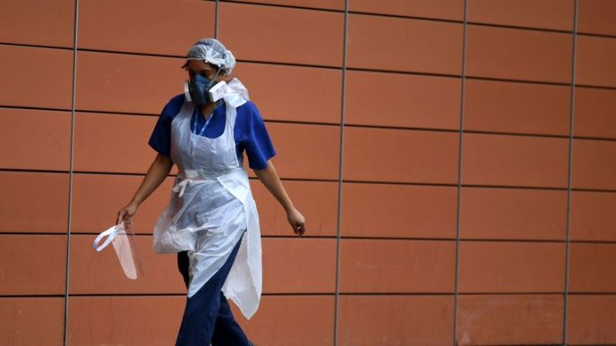 A nurse wears a face mask as she walks past the Royal London Hospital in east London