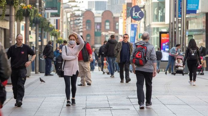 Some people wear face masks as they walk past Dublin stores