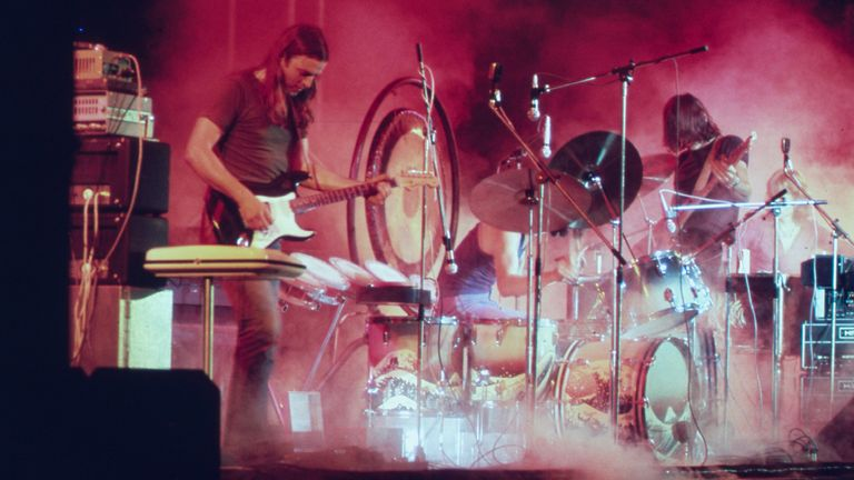 Pink Floyd playing on the stage surrounded with a smoke and illuminated with a red stage lights during the concert at Merriweather Post Pavilion, Columbia, Maryland in June 1973, July, 1973. Image courtesy National Archives. (Photo by Smith Collection/Gado/Getty Images)