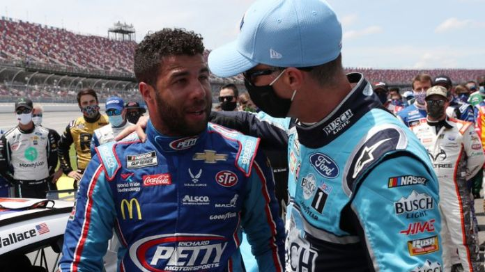TALLADEGA, ALABAMA - JUNE 22: Bubba Wallace, driver of the no. 43 to the Victory Junction Chevrolet, is hosted by Kevin Harvick, driver of the # 4 Busch Light Ford, after the NASCAR drivers pushed Wallace to the front of the grid as a sign of solidarity with the driver prior to the NASCAR Cup GEICO 500 at Talladega Superspeedway on June 22, 2020 Talladega, Alabama. A noose was found in the garage stall of NASCAR driver Bubba Wallace at Talladega Superspeedway one week after the organization banned the flag Confederate to its facilities. (Photo by Chris Graythen/Getty Images)