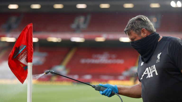 Groundstaff disinfect a corner flag during the English Premier League football match between Liverpool and Crystal Palace at Anfield in Liverpool, north west England on June 24, 2020. (Photo by PHIL NOBLE / POOL / AFP) / RESTRICTED TO EDITORIAL USE. No use with unauthorized audio, video, data, fixture lists, club/league logos or 'live' services. Online in-match use limited to 120 images. An additional 40 images may be used in extra time. No video emulation. Social media in-match use limited to 120 images. An additional 40 images may be used in extra time. No use in betting publications, games or single club/league/player publications. /  (Photo by PHIL NOBLE/POOL/AFP via Getty Images)