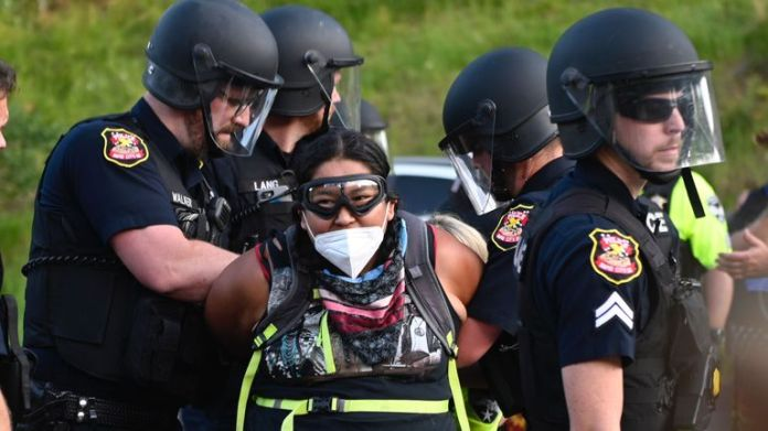 Police arrest protester wearing face mask as activists and members of various tribes in the area blocked the road to Mount Rushmore National Monument in Keystone, South Dakota, July 3, 2020, during a demonstration around the Mount Rushmore National Monument and the visit to the United States.  President Donald Trump.  (Photo by ANDREW CABALLERO-REYNOLDS / AFP) (Photo by ANDREW CABALLERO-REYNOLDS / AFP via Getty Images)