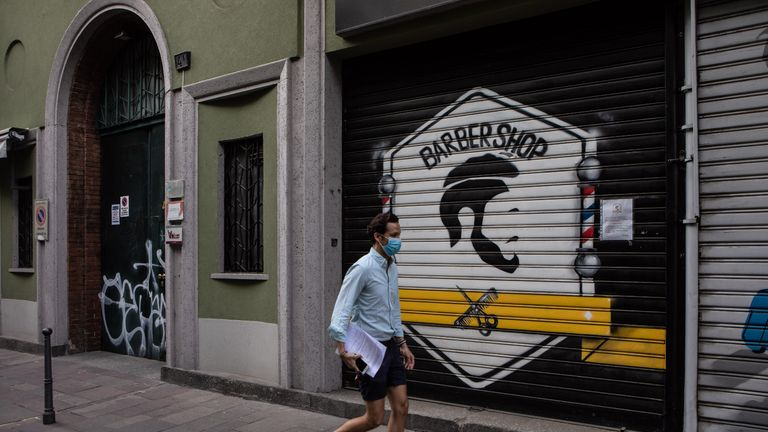 MILAN, ITALY - MAY 06: A man, wearing a protective face mask, walks past a shuttered barber shop on May 06, 2020 in Milan, Italy. Italy was the first country to impose a nationwide lockdown to stem the transmission of the Coronavirus (Covid-19), and its restaurants, theaters and many other businesses remain closed. (Photo by Emanuele Cremaschi/Getty Images)