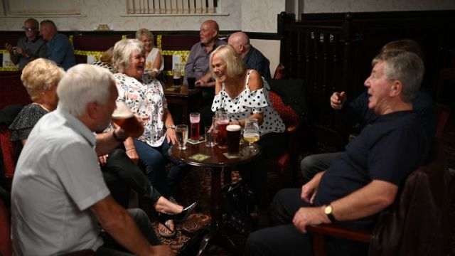 People enjoy a drink with yellow tape on the seats aiding social distancing inside the Burnley Miners Working Men's Social Club