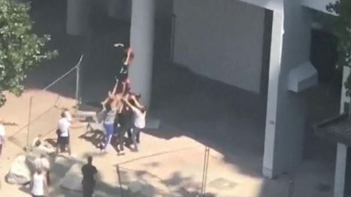 One of the boys is seen falling in the crowd