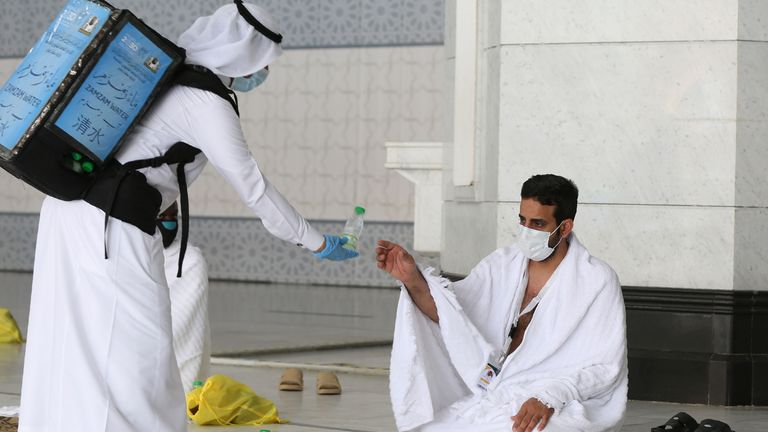 A pilgrim receives water at the Grand Mosque complex in Mecca