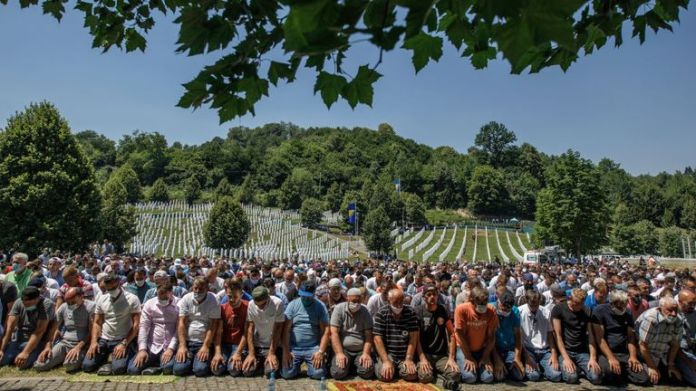 Bosnian Muslims pray during the mass funeral at the Potocari memorial and cemetery near Srebrenica