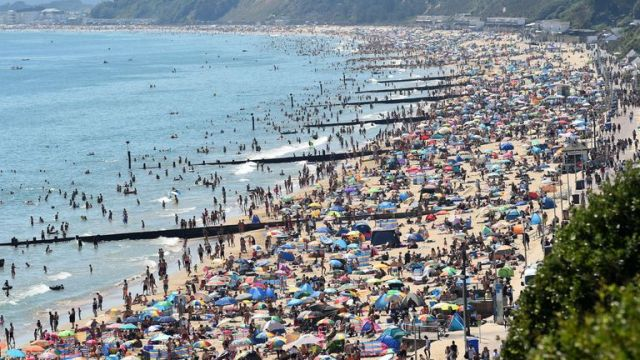 TOPSHOT - Beachgoers enjoy the sunshine as they sunbathe and play in the sea on Bournemouth beach in Bournemouth, southern England, on June 25, 2020. - Just days after lockdown ended and European travel restrictions were lifted, many were staying home in the cool as a heatwave hit the continent with temperatures touching 40 degrees Celcius. Britain was bracing for a flood of visitors to its beaches with the heatwave expected to last until Friday and temperatures set to climb into the mid-30s in the south and centre of the country. (Photo by Glyn KIRK / AFP) (Photo by GLYN KIRK/AFP via Getty Images)