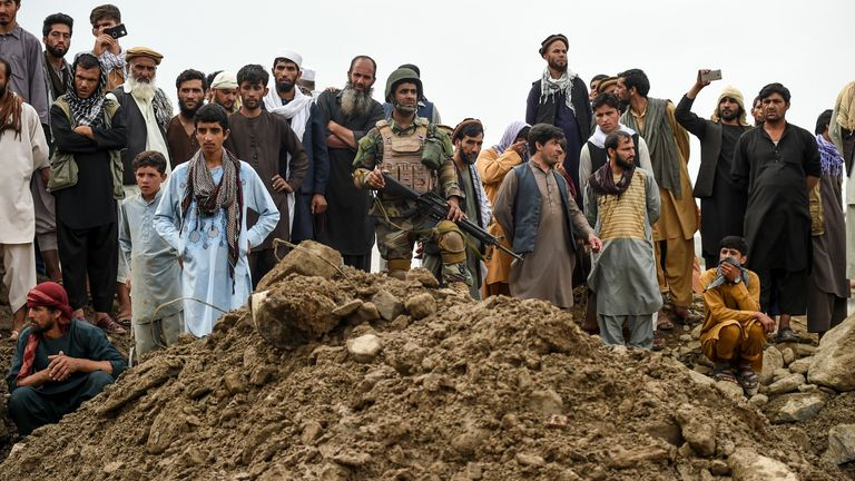 A security personnel (C) stands guard among villagers gathering as rescuers search for bodies in Parwan province