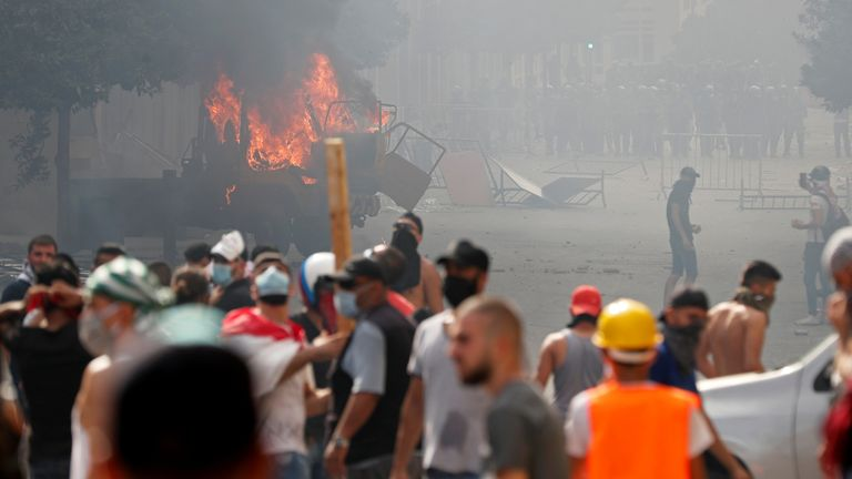 A vehicle burns as demonstrators try to break through a barrier near the parliament building