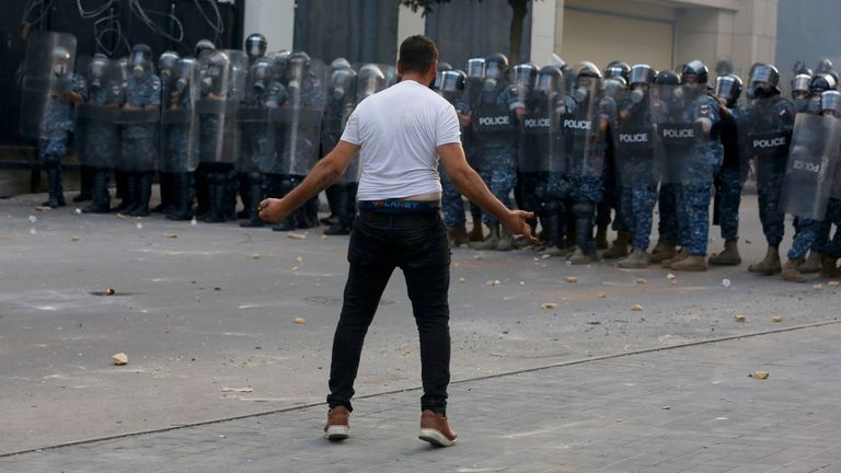 A lone protester confronts security forces during an anti-government protest at Lebanon's parliament in Beirut