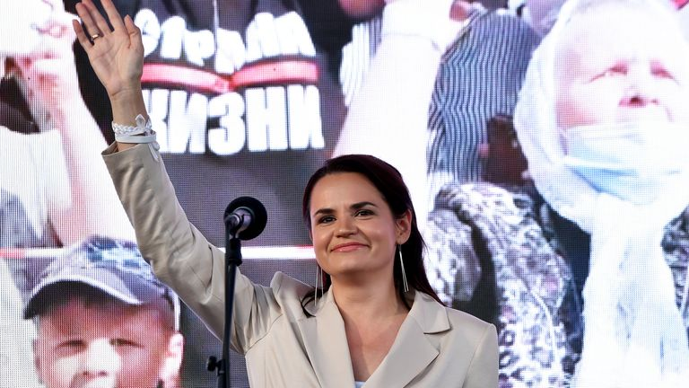 Presidential candidate Svetlana Tikhanovskaya waves to supporters at a rally in July
