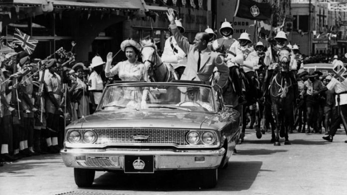 February 18, 1966: The Queen and Prince Philip cross Barbados waving to the crowd.  (Photo by Keystone / Getty Images)