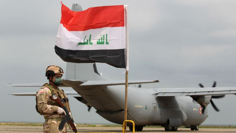 An Iraqi soldiers stands guard in front US military air carrier at the Qayyarah air base