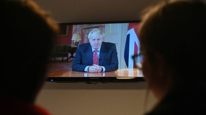 Family members watch British Prime Minister Boris Johnson address the nation about the latest updates on the restrictions of the novel coronavirus COVID-19, on their television at their home in Liverpool on September 22, 2020. - Britain tightened restrictions on Tuesday to stem an outbreak of coronavirus cases, ordering pubs to close early and advising people to return to work from home to avoid a second nationwide lockdown.
