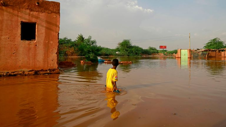 A Sudanese boy wades through a flooded street at the area of al-Qamayir in the capital's twin city of Omdurman, on August 26, 2020