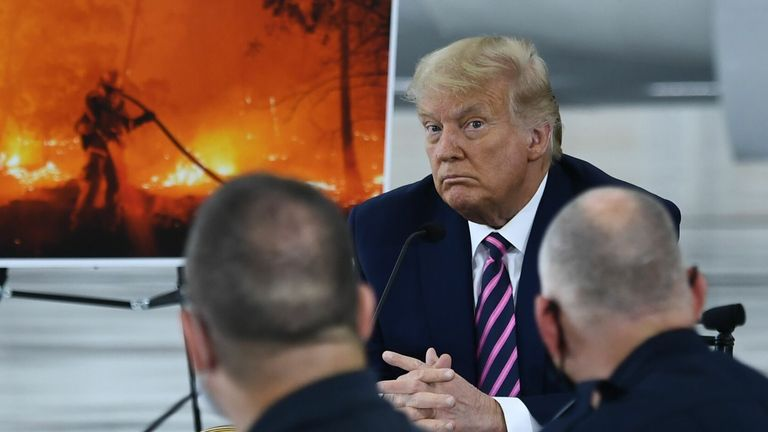 US President Donald Trump(C) listens to California Governor Gavin Newsom(D-CA) at Sacramento McClellan Airport in McClellan Park, California on September 14, 2020 during a briefing on wildfires. (Photo by Brendan Smialowski / AFP) (Photo by BRENDAN SMIALOWSKI/AFP via Getty Images)