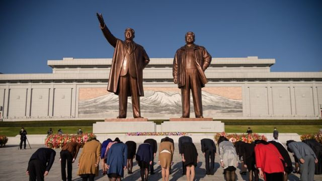 People bow before the statues of late North Korean leaders Kim Il Sung and Kim Jong Il at Mansu hill as the country marks the 75th founding anniversary of the Workers' Party of Korea, in Pyongyang on October 10, 2020. (Photo by KIM Won Jin / AFP) (Photo by KIM WON JIN/AFP via Getty Images)