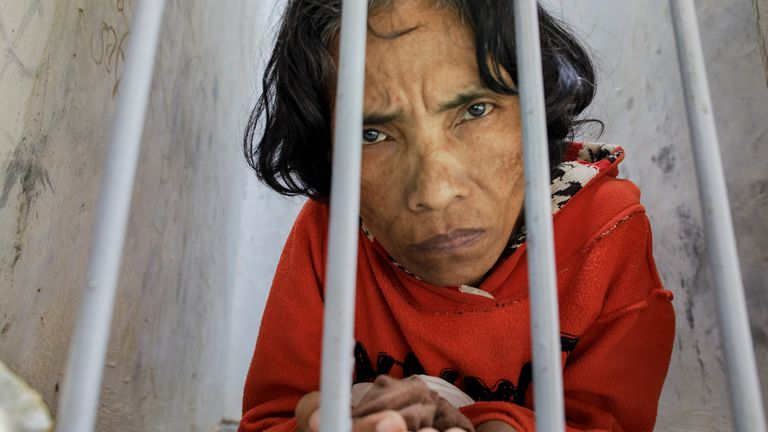 A woman with a psychosocial disability lives confined in a bare narrow cell at madrasah Ar-Ridwan, a private Islamic healing center in Cilacap, Central Java, Indonesia.
