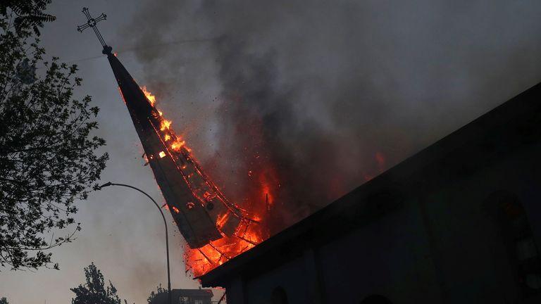 A torre de uma igreja em chamas cai no chão após ser incendiada na capital chilena