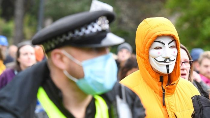 BOURNEMOUTH, ENGLAND - NOVEMBER 21: An anti-lockdown protester is seen in a Guy Fawkes mask as the march heads through the town centre on November 21, 2020 in Bournemouth, England. (Photo by Finnbarr Webster/Getty Images)