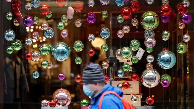 People walk in the rain past Christmas decorations in central London on November 20, 2020, as life under a second lockdown continues in England. - The current lockdown in England has shuttered restaurants, gyms and non-essential shops and services until December 2, with hopes business could resume in time for Christmas. (Photo by Tolga Akmen / AFP) (Photo by TOLGA AKMEN/AFP via Getty Images)