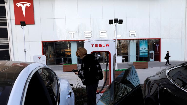 A woman charges a Tesla car in front of the electric vehicle maker's showroom in Beijing, China on Jan. 5, 2021