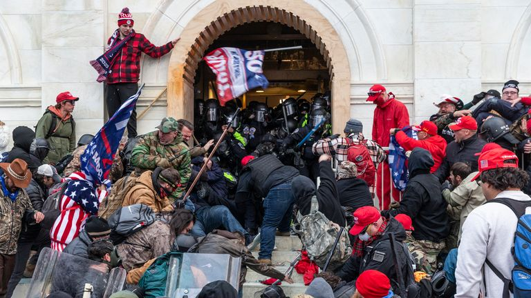 WASHINGTON DC, COLOMBIA DISTRICT, UNITED STATES - 01/2021/06: Rioters clash with police trying to enter the Capitol through the front doors. Rioters broke windows and broke into the Capitol to overturn the results of the 2020 election. Police used batons and tear gas grenades to disperse the crowd. Rioters also used metal bars and tear gas against the police. (Photo by Lev Radin / Pacific Press / LightRocket via Getty Images)