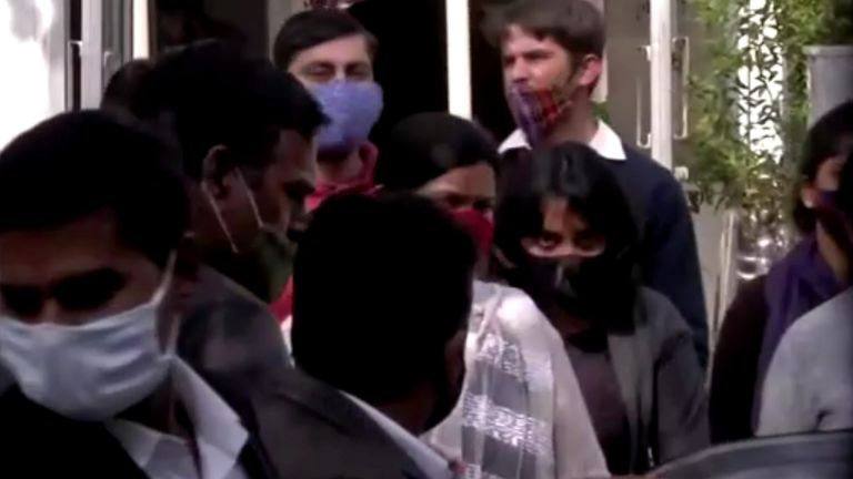 Climate change activist Disha Ravi is escorted by police officials as she walks out of the court in New Delhi, India