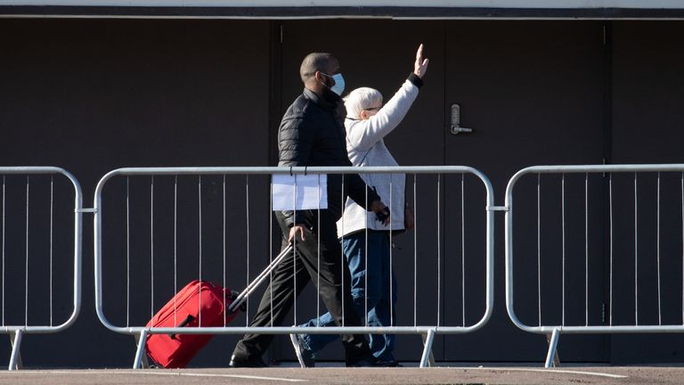 A person waves as they leave the Radisson Blu Edwardian hotel after completing their quarantine