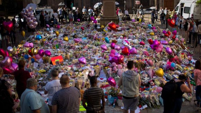 People stand next to flowers for the victims of Monday's bombing at St Ann's Square in central Manchester, England, Friday, May 26 2017. British police investigating the Manchester Arena bombing arrested a ninth man while continuing to search addresses associated with the bomber. (AP Photo/Emilio Morenatti)