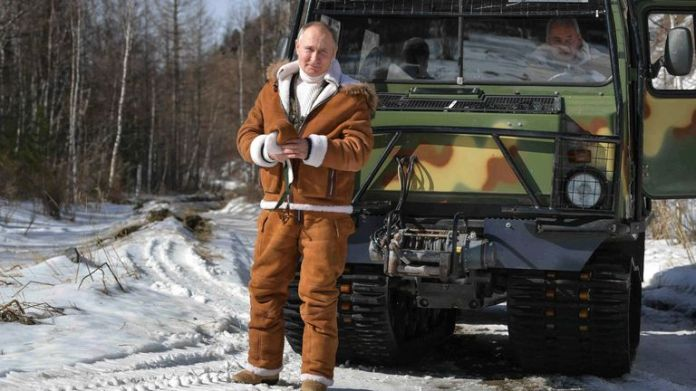 Putin poses for a photo in front of a tracked all-terrain vehicle