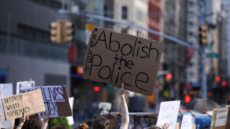 Protesters hold placards during a protest against police brutality in the wake of George Floyd's death in Manhattan, New York