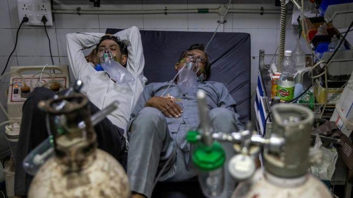 En raison d'une pénurie de lits dans les hôpitaux, les patients sont obligés de partager leurs lits pendant qu'ils reçoivent un traitement contre le virus.