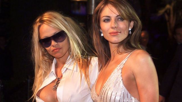 Actresses Pamela Anderson and Elizabeth Hurley pose together as they arrive at the Vanity Fair post-Academy Awards party at Mortons in Los Angeles, March 25, 2001