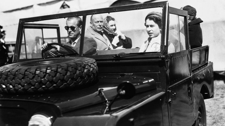 Queen Elizabeth II sits in the front seat of a Land-Rover vehicle as her husband, the Duke of Edinburgh, drives on the grounds of Windsor Great Park in London, England, May 19, 1955