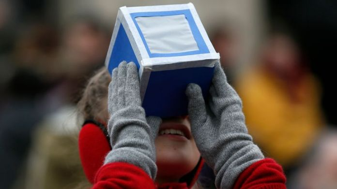 A girl holds a home-made protective viewing box outside The Royal Observatory during a partial solar eclipse in Greenwich, south east London March 20, 2015. REUTERS/Stefan Wermuth