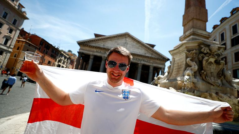 A fan poses with an England flag in front of the Pantheon in Rome