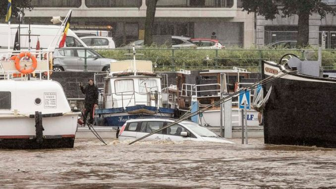 A car is submerged between two boats in the Meuse river during flooding in Liege, Belgium. Pic: AP