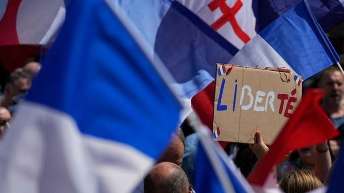 A protestor waves a sign which reads 'freedom' in the middle of French flags during a demonstration in Paris, France, Saturday, July 31, 2021. Demonstrators gathered in several cities in France on Saturday to protest against the COVID-19 pass, which grants vaccinated individuals greater ease of access to venues. (AP Photo/Michel Euler)