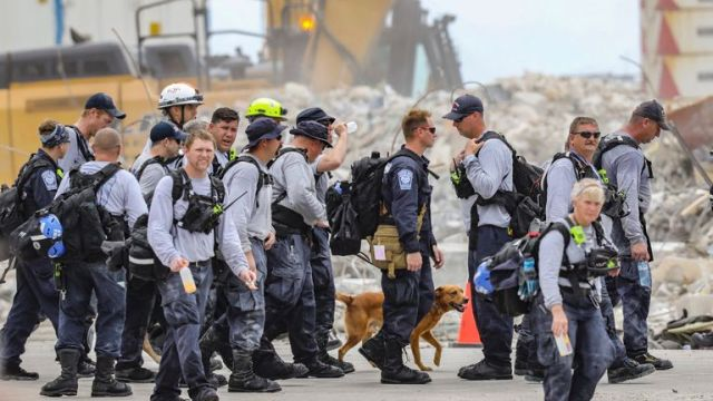 Search and rescue team members depart after working the debris field of the 12-story oceanfront condo, Champlain Towers South in Surfside on Wednesday, July 7, 2021.