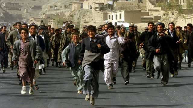 FILE PHOTO: Residents of Kabul celebrate and escort Northern Alliance fighters entering the Afghan capital Kabul, Afghanistan November 13, 2001. REUTERS/Yannis Behrakis/File Photo