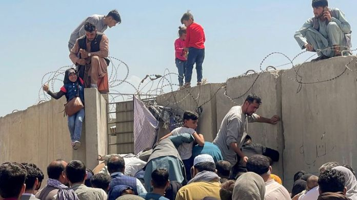 A man pulls a girl up a wall to get inside the Hamid Karzai International Airport in Kabul.