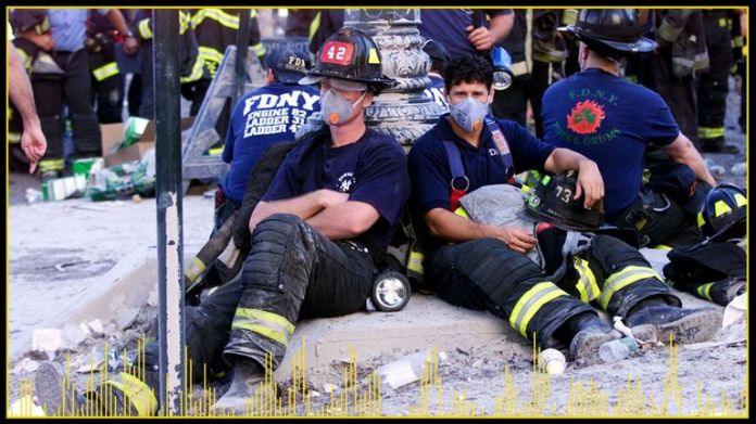 Firefighters rest near the wreckage of the World Trade Center after planes hit each of the two towers