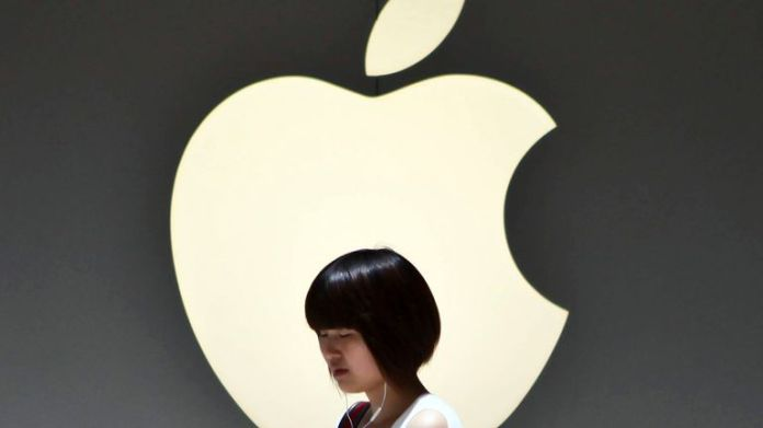 A girl walks past the Apple logo outside an Apple store in Shanghai, China on Monday July 2, 2012. Apple has paid $60 million to settle a dispute in China over ownership of the iPad name, a court announced Monday, removing a potential obstacle to sales of the popular tablet computer in the key Chinese market.   (AP Photo) CHINA OUT