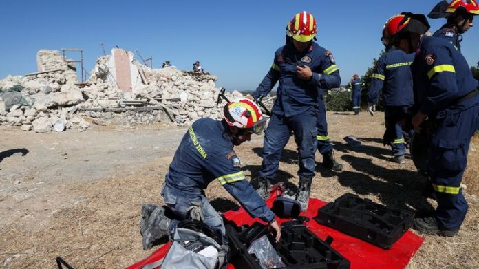 Firefighters check their gear next to the rubble of a demolished church, following an earthquake, in the town of Arkalochori on the island of Crete, Greece